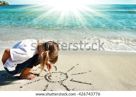a small child playing on the shore of the sea - stock photo