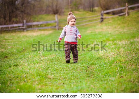A small child plays with a Frisbee outdoors in the woods.
