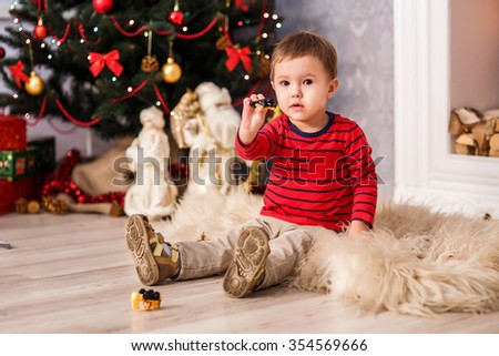 a small child plays with toys near the Christmas tree. Christmas and new year - stock photo
