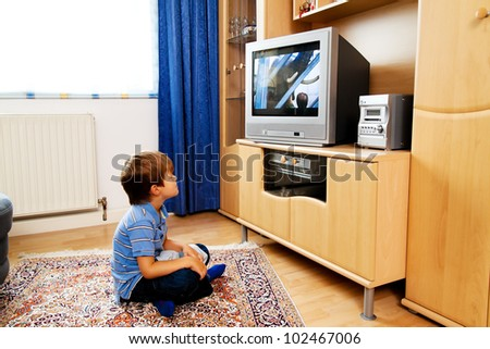 a small child watching television with tv - stock photo