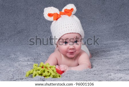 A small child with a rabbit ears. Lying on his stomach with a carrot. - stock photo