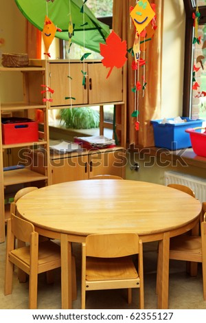 A small children's table with children's chairs in front of a shelf with toys - stock photo