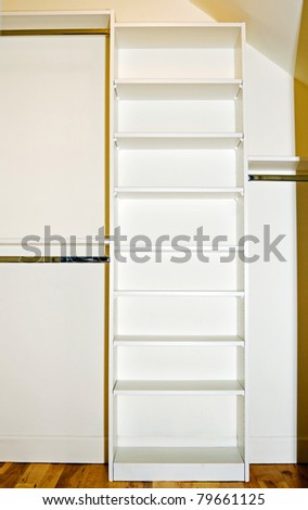 A small closet interior showing the organizer shelving and rods. - stock photo