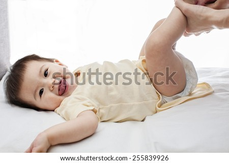 A small cute little baby girl was lying down, her diaper was being changed by her father, closeup, white background, studio