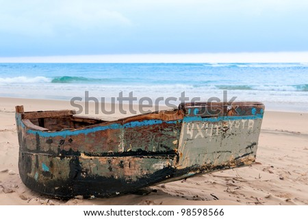 a small dugout boat on the sand - stock photo