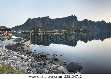 A small fishing port in the Hamnoy with Lilandstinden mountain peak on the background - Reine, Lofoten Islands, Norway - stock photo