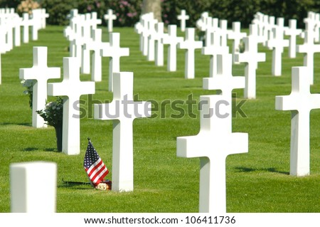 A small flag of the US between cross headstones at the American military cemetery in the Netherlands - stock photo