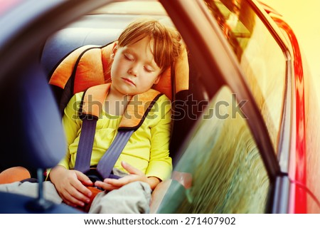 a small girl sleeps in car - stock photo
