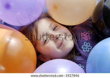 a small girl surrounded with balloons - stock photo