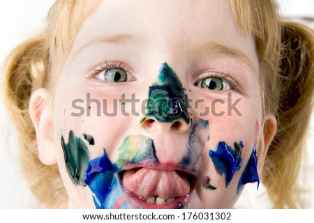 A small girl with paint all over her face. - stock photo