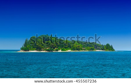 a small green island in the calm sea in warm summer day - stock photo