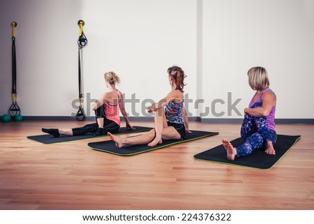 A small group of women are stretching their backs in the gym