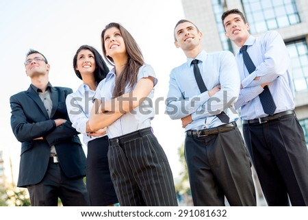 A small group of young business people standing in front of office building with arms crossed and with a smile on their faces looking in height.