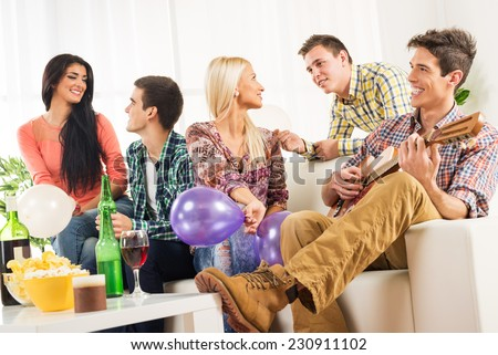 A small group of young people hang out at the house party, chatting with each other while their friend having fun playing acoustic guitar. - stock photo