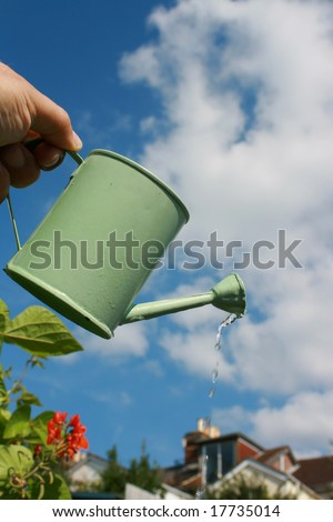 A small hand held watering can being held aloft against an urban garden scene.Water emerging from spout of watering can.
