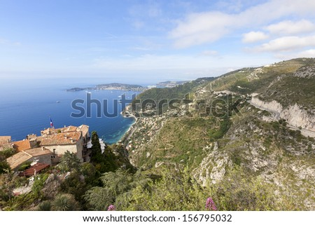 A small hilltop village called Eze with views out to the ocean and the 3 scenic roads known as the corniches. Blue sky with a few clouds. South of France, French Riviera, Europe.
