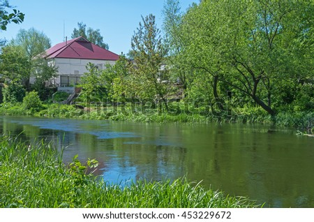 A small house near a river surrounded by trees warm spring day