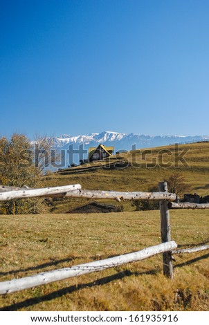 A small house on a hill, with snow capped mountains in the background and fence in the foreground - stock photo