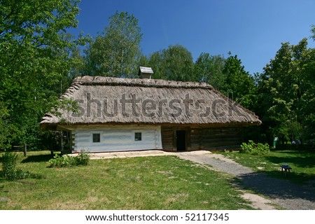 A small house with a thatched roof around a lot of green trees
