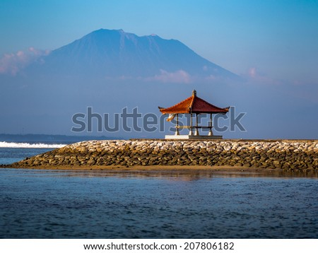 a small hut on the shore with mountain background - stock photo