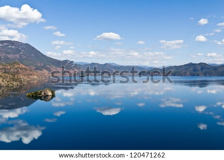 A small island floats on the mirror lake - stock photo