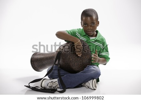 A small isolated African American male child in a green shirt studying how to play a djembe drum against a white background.
