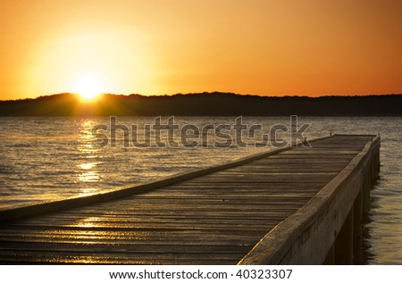 A small jetty sticks out onto the lake at sunrise - stock photo