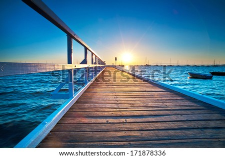 A small jetty sticks out onto the water at sunrise. - stock photo