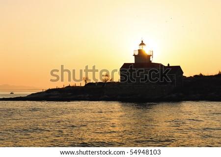 A small lighthouse at sunset. Croatia. - stock photo