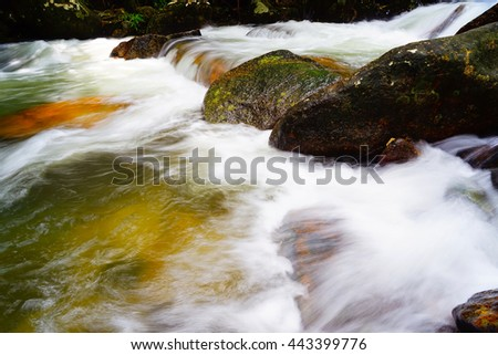 A small moorland stream cascading over a weir captured using a slow shutter speed to blur the movement of the water,select focus with shallow depth of field:ideal use for background. - stock photo