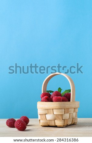 A small natural woven basket, filled with raspberries, with three grouped on the wooden surface beside it.  Blue background. - stock photo