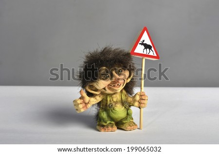 A small norwegian troll hitchhiking and holding a road sign with an elk - stock photo