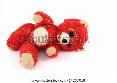 A small old worn teddy bear on white