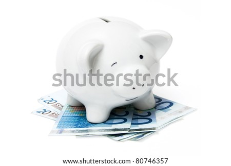 A small piggy bank with euro banknotes isolated on a white background - stock photo