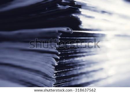 A small pile of thin magazines closeup - stock photo