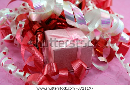A small pink gift box is nestled into a pile of curly red and heart patterned curly ribbons.