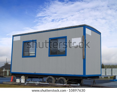 A small portable office on wheels at a construction site on a warm sunny day. - stock photo