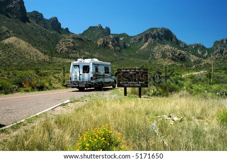 A small recreational vehicle navigates past a bear and mountain lion warning in big Bend National Park.