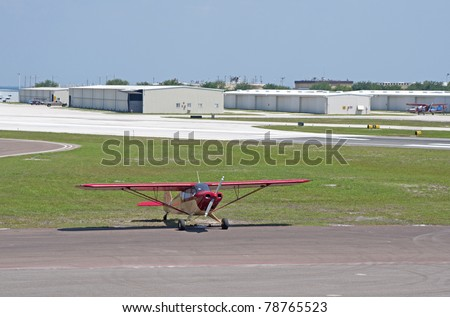 A small red propeller airplane parked at an airport hangar in St. Petersburg Florida. - stock photo