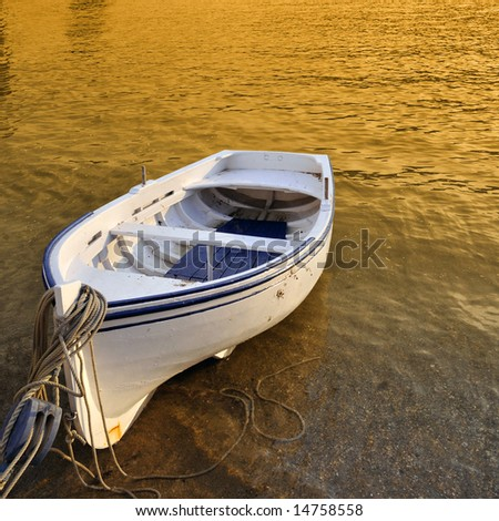 A small row boat beached on the shore at sunset - Cadaques, Spain - stock photo