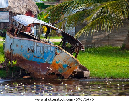 A small rusted, abandoned ferry in the town of Bomba, Belize - stock photo