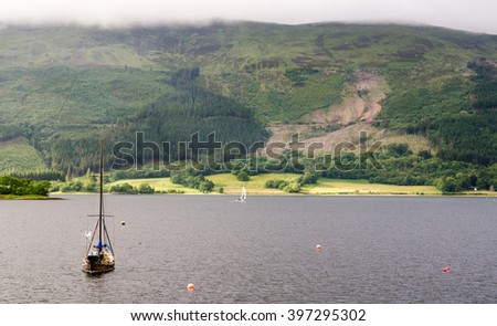 A small sail boat sheltering in Loch Leven, the sea loch beside Glen Coe in the West Highlands of Scotland. - stock photo