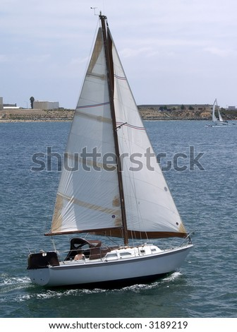 A small sail boat speeds along in San Diego Harbor on an overcast day - stock photo
