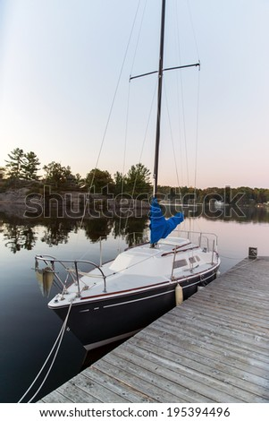 A small sailboat sits docked on a calm lake during the evening.  - stock photo