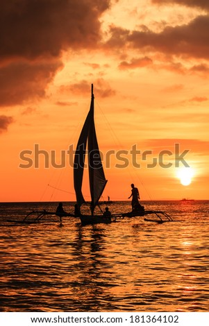A small sailing boat in silhouette against a tropical sunset on a calm ocean - stock photo
