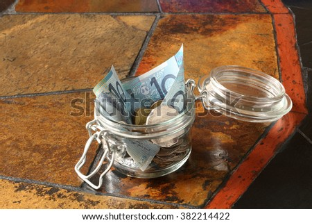 A small 'savings' jar containing Australian money, both coins and notes, shown on a table top made from tiles and which has space for your text - stock photo