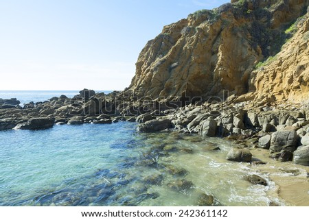 A small, secluded ocean front cove with large, smooth boulders embraces gentle surf bouncing off the large rocks - stock photo
