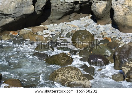 A small shoreline cove in rugged terrain along the shores of California shows the large boulders and rocky wilderness. - stock photo