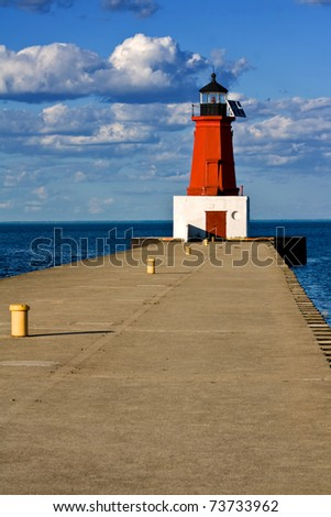 a small solar-powered lighthouse at the end of a jetty - stock photo