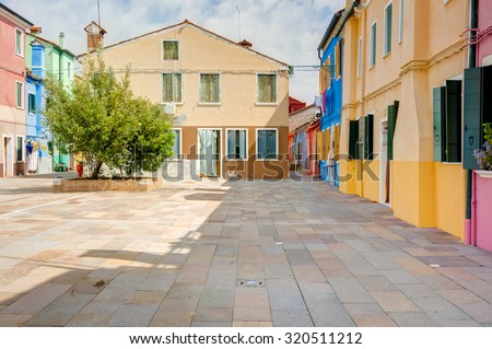 A small square in Burano island, with the typical colorful houses. Venice, Italy. Taken on August 21, 2015 - stock photo